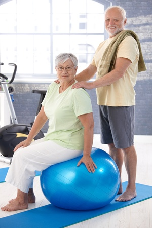 boomers: Smiling old couple relaxing after workout, man giving massage to woman. Stock Photo