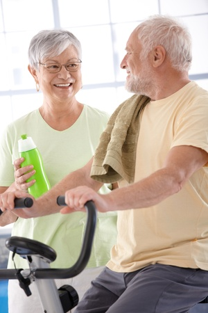 elderly exercise: Happy elderly couple in the gym, man on fitness cycle.