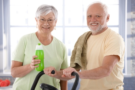 elderly exercise: Portrait of happy senior couple in the gym, looking at camera. Stock Photo