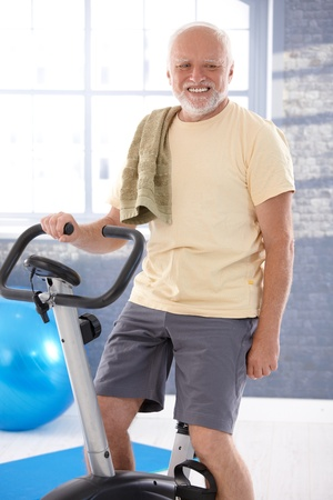 boomers: Senior man exercising on fitness cycle, smiling. Stock Photo