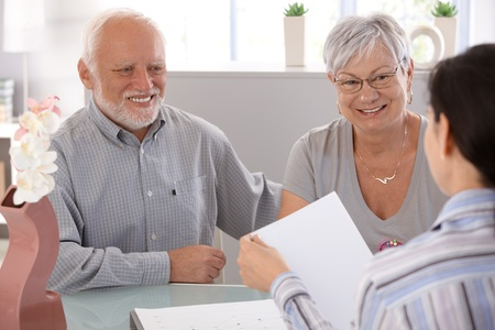 older women: Senior couple sitting at desk at financial advisor, smiling.