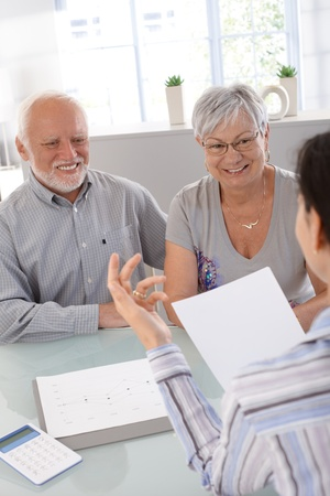 consulting room: Elderly couple at financial consultation, smiling.