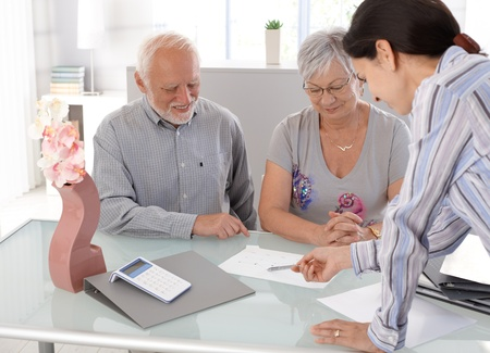 color consultation: Happy senior couple looking at chart at financial advisor.