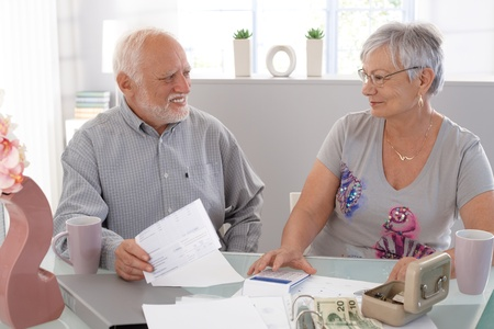 Smiling senior couple discussing financial matters at home. photo