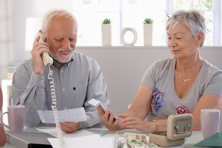 Elderly couple checking bills at home, discussing finances. photo