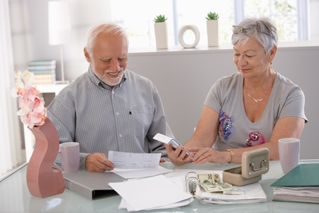 Happy senior couple calculating family budget at home. photo