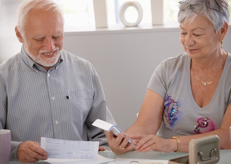 Elderly couple calculating budget, checking bills at home, smiling. photo