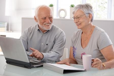 Senior people using laptop computer, smiling. photo