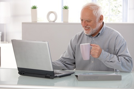 Elderly man working on laptop, smiling, looking at screen, drinking tea. Stock Photo