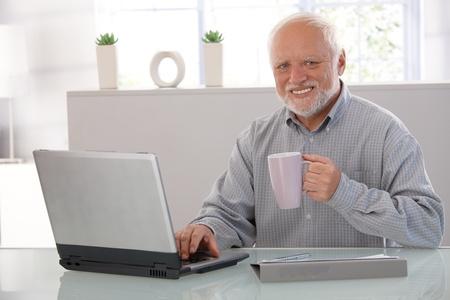 Mature man using computer, drinking tea, looking at camera, smiling.