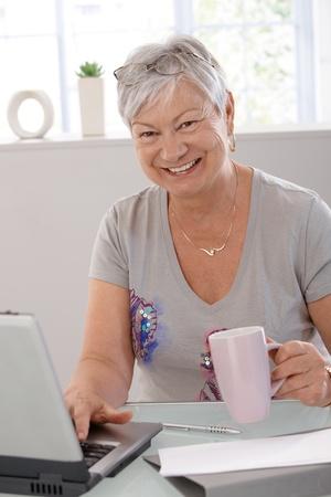 Happy elderly woman using laptop computer, smiling, drinking tea. photo