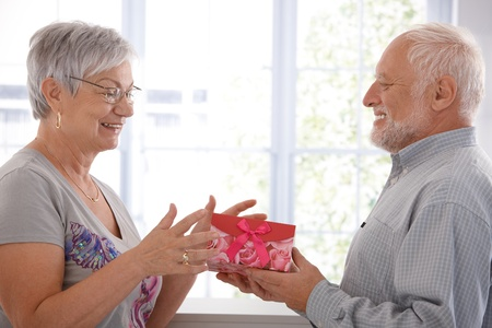 receiving: Senior female getting present from husband, smiling.