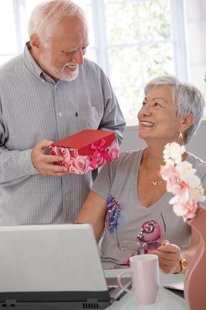 ambos: Hombre maduro da presente a su esposa, ambos sonriendo alegremente.
