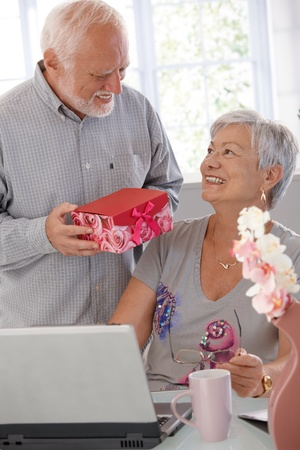 Mature man giving present to wife, both smiling happily. photo