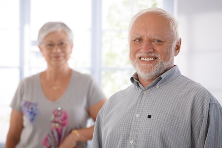 older men: Portrait of happily smiling old man, woman in the background.