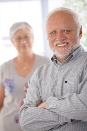 Portrait of happy confident old man, woman at background. photo