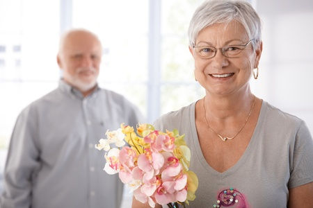 Portrait of smiling senior woman holding flowers, man at background. photo