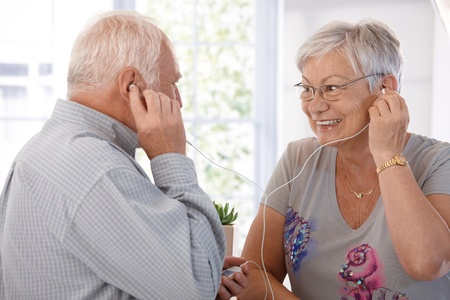 Elderly couple listening to music on mp3 player, smiling. Stock Photo
