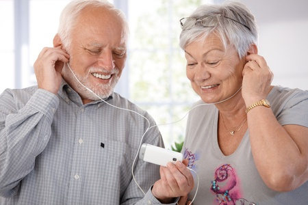 listen to music: Senior couple using mp3, listening to music, smiling. Stock Photo