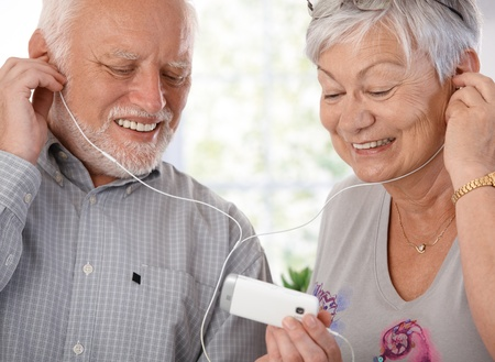Happy elderly couple using mp3 player, listening to music, smiling.