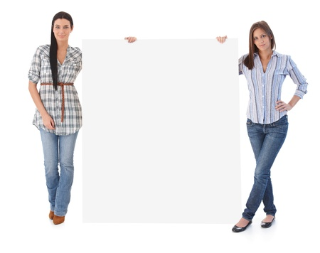 top: Attractive young women holding huge blank sheet. Stock Photo