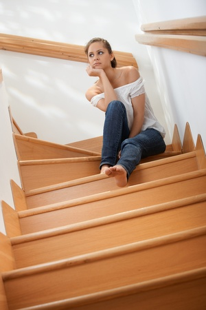 Pretty young girl sitting at staircase, thinking, looking away. Stock Photo - 10377669