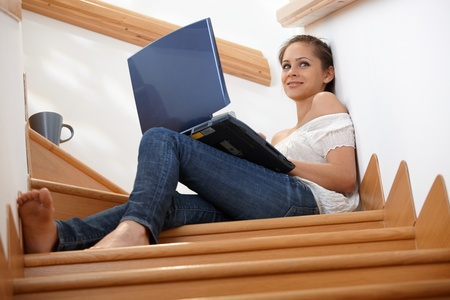 full size: Attractive girl sitting at staircase, using laptop computer, smiling.