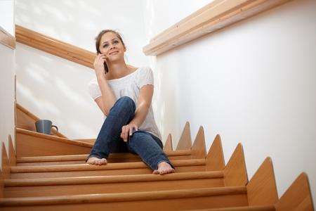 alumnos en clase: Sonriente joven sentado en las escaleras en casa, hablando por teléfono móvil.