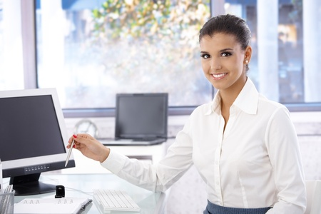 Happy young woman working in bright office, looking at camera. photo