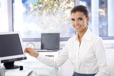 jornada de trabajo: Mujer joven feliz trabajando en la Oficina brillante, mirando a la cámara.