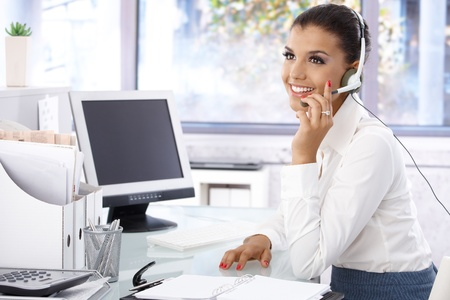 Attractive young dispatcher working in bright office, sitting at desk, smiling. photo