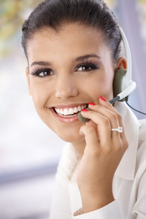 Closeup portrait of beautiful young dispatcher, smiling, looking at camera. Stock Photo