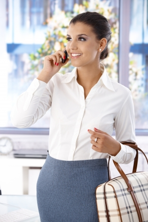 blouse: Pretty young woman chatting on mobile phone, smiling, looking away. Stock Photo