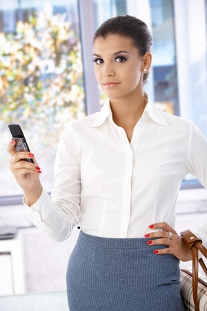 Attractive young businesswoman using mobile phone. photo