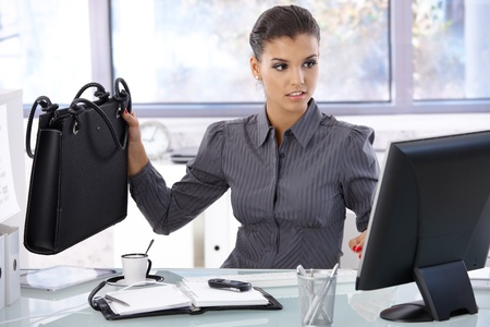 Busy businesswoman working at desk in bright office. photo