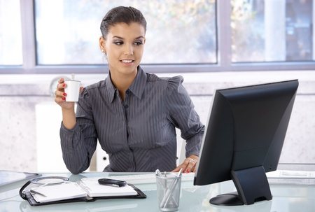 organizer: Young businesswoman sitting at desk, working on computer, drinking coffee.