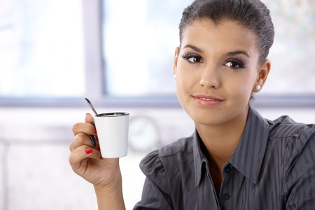 Portrait of attractive young businesswoman with coffee cup. photo