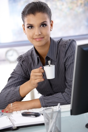 Beautiful young businesswoman drinking coffee, smiling, looking at camera. photo