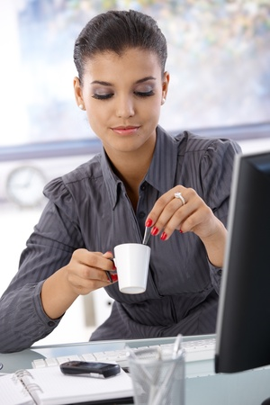 Pretty businesswoman sitting at desk in bright office, drinking coffeee. photo