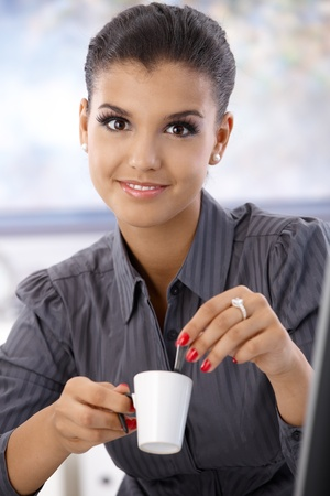 Portrait of young attractive businesswoman drinking coffee, smiling. photo