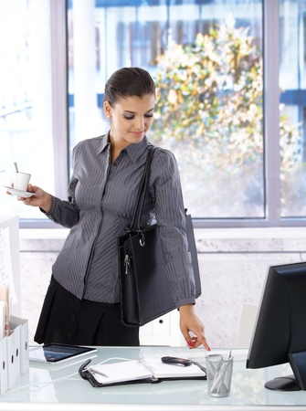 Busy woman arriving at office, drinking coffee. photo