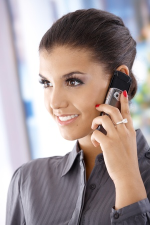 Attractive young smiling woman talking on mobile phone. Stock Photo - 10377647