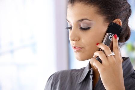 prestar atencion: Closeup retrato de joven mujer hablando por teléfono móvil. Foto de archivo