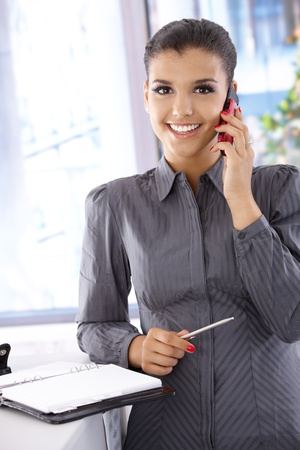 Beautiful businesswoman talking on mobile phone, smiling, looking at camera. photo
