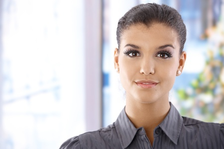 Portrait of pretty young woman, smiling, looking at camera. photo