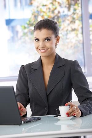 blazer: Beautiful woman working on laptop, smiling, looking at camera.