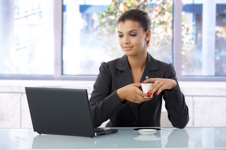 Young woman using laptop in bright office, drinking coffee. photo
