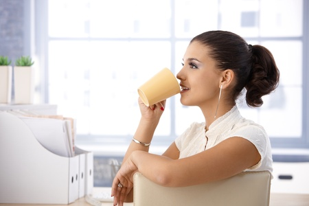 Pretty female casual office worker drinking tea in bright office. Stock Photo - 10377581