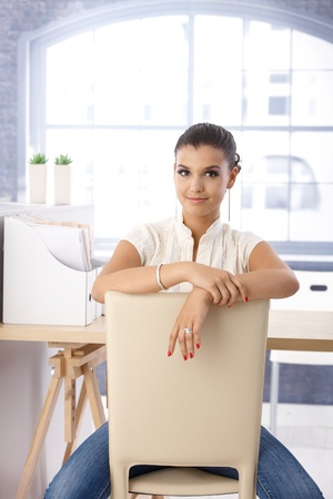 Attractive girl sitting conversely on chair on bright office. photo