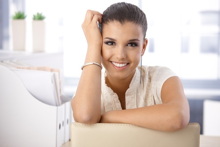 satisfied: Portrait of beautiful young smiling girl in office. Stock Photo